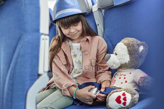 Девушка, крепления ремней на чучело на самолете — стоковое фото