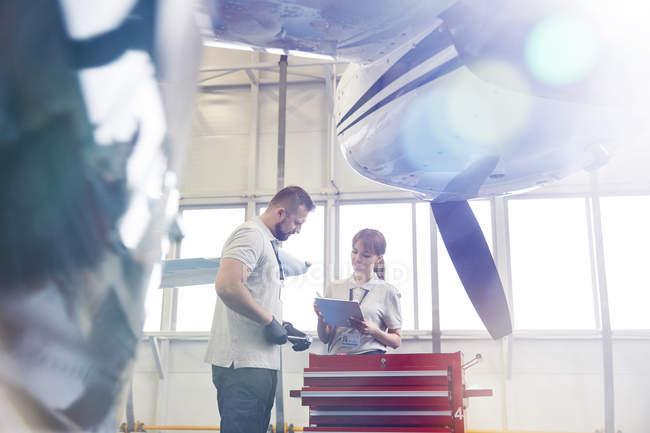 Mecánicos de avión con portapapeles en caja de herramientas en hangar - foto de stock