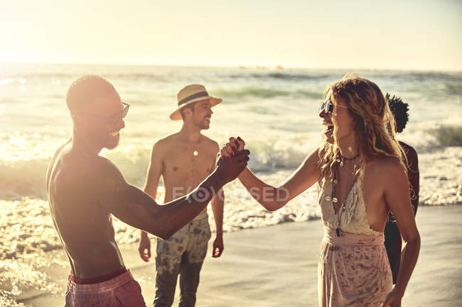 Playful young couple high-fiving on sunny summer ocean beach — Stock Photo
