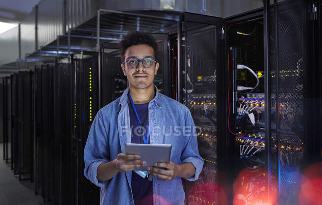 Portrait confident male IT technician with digital tablet in server room — Stock Photo
