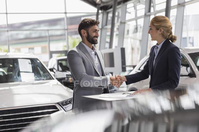 Commerciante di auto e cliente maschio stretta di mano in concessionaria auto showroom — Foto stock