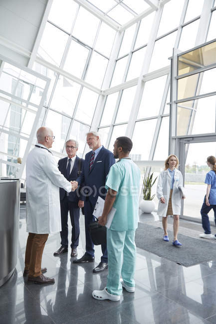 Male surgeon greeting, shaking hands with administrator businessmen in hospital lobby — Stock Photo