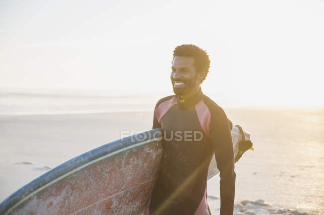 Smiling male surfer walking with surfboard on sunny summer beach — Stock Photo