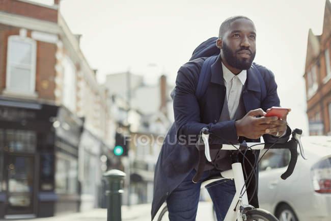 Giovane uomo d'affari pensieroso che messaggia con il cellulare, pendolarismo in bicicletta sulla strada urbana — Foto stock
