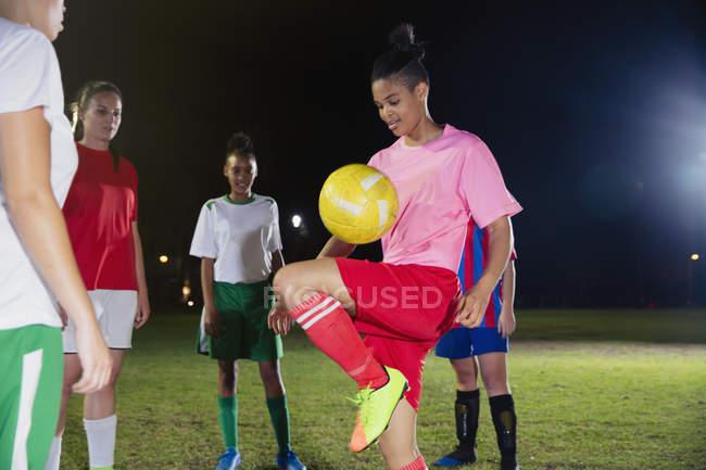Junge Fußballerin übt, hüpft nachts Ball auf Knie auf dem Feld — Stockfoto