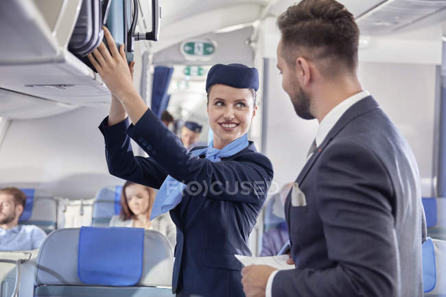 Flight attendant helping businessman with luggage on airplane — Stock Photo