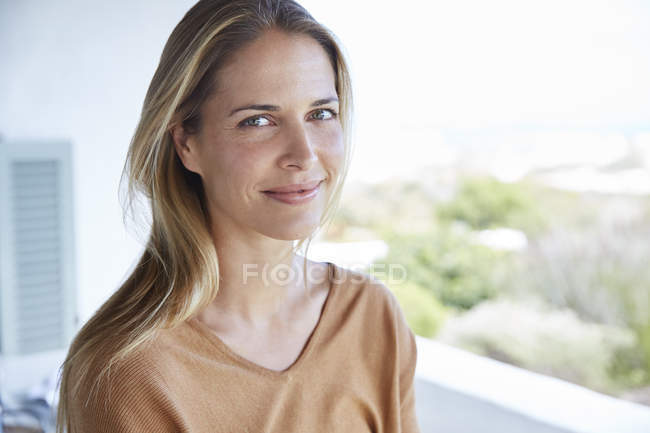 Portrait smiling blonde woman on patio — Stock Photo