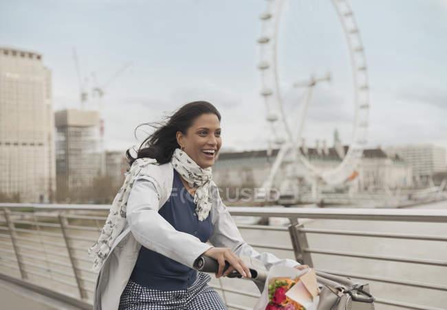 Enthusiastic, smiling woman bike riding on bridge near Millennium Wheel, London, UK — Stock Photo