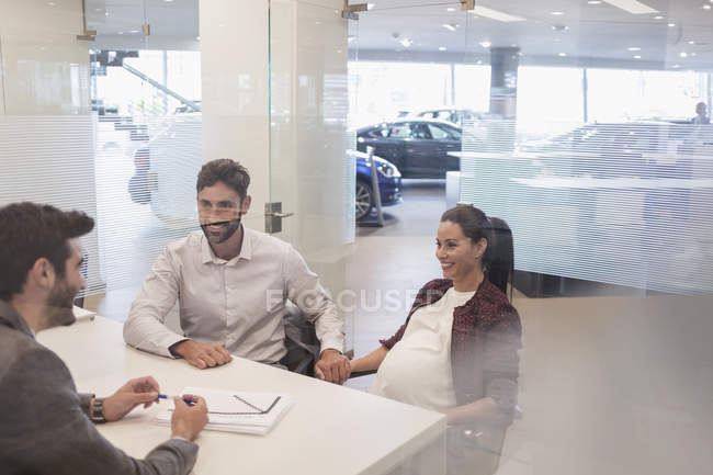 Car salesman talking to pregnant couple in car dealership office — Stock Photo
