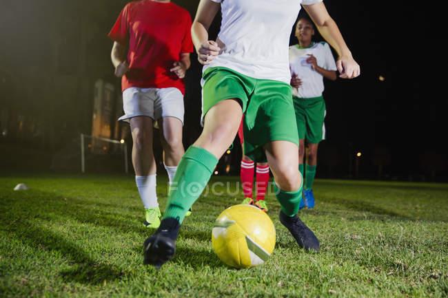 Junge Fußballspielerinnen, die nachts auf dem Feld spielen und gegen den Ball treten — Stockfoto