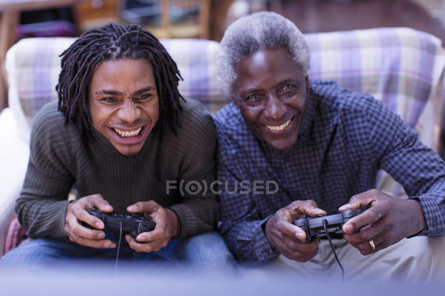 Happy grandfather and grandson playing video game — Stock Photo