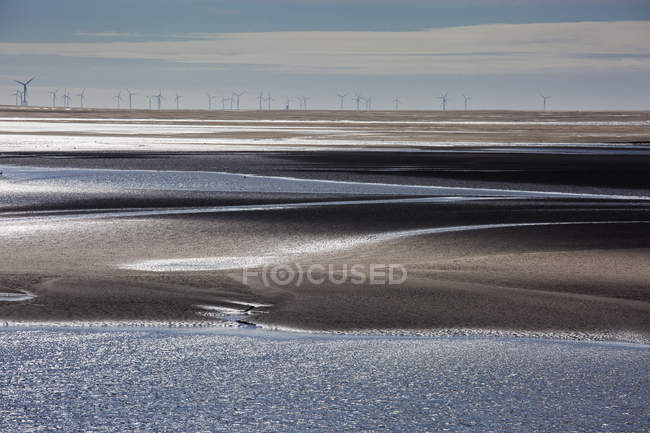 Wind turbines in distance beyond bay, Morecambe Bay, UK — Stock Photo