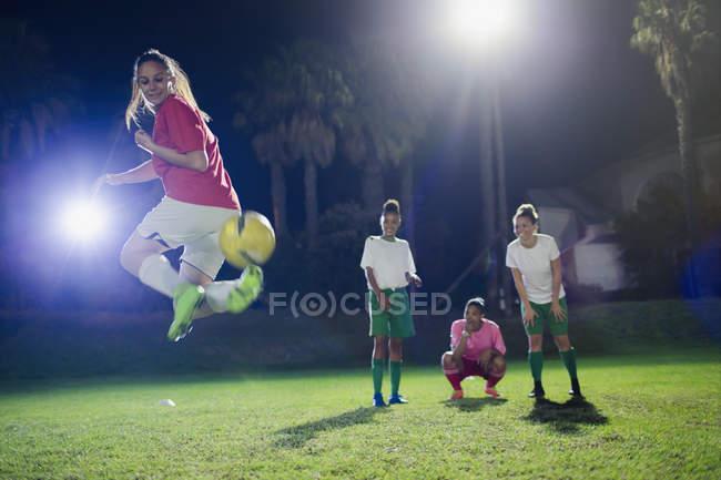 Молодые футболистки практикуются на поле по ночам, делают ответный удар — стоковое фото