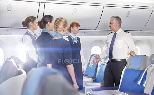 Piloto y azafatas hablando, preparando en avión - foto de stock