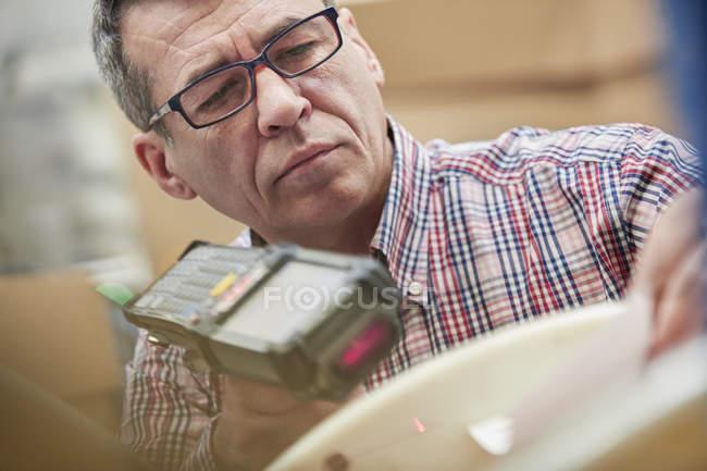 Trabajador masculino enfocado usando escáner de código IR en almacén de fibra óptica - foto de stock