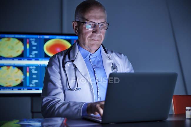 Cirurgião masculino focado trabalhando em laptop no hospital — Fotografia de Stock