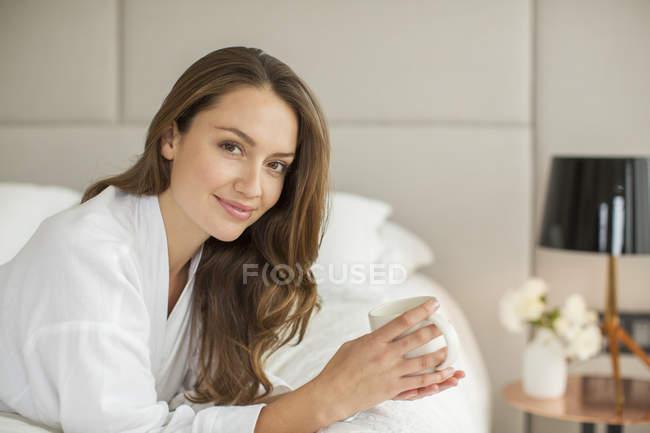 Портрет улыбается женщина в Халат, пить кофе на кровати — стоковое фото