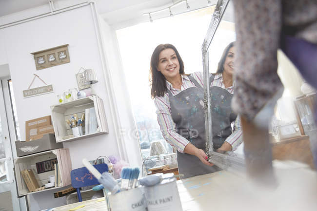 Smiling female artists moving painted mirror in art class workshop — Stock Photo