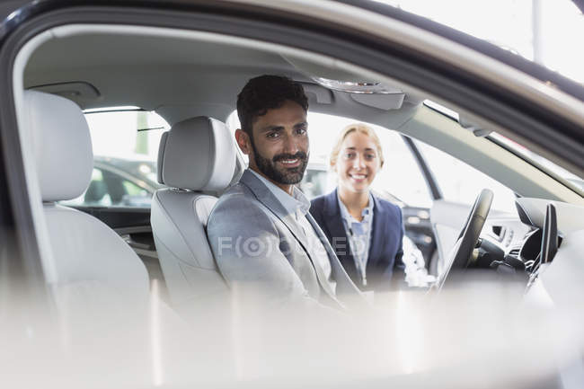 Portrait smiling, confident car saleswoman and male customer in driver?s set of new car in car dealership — Stock Photo