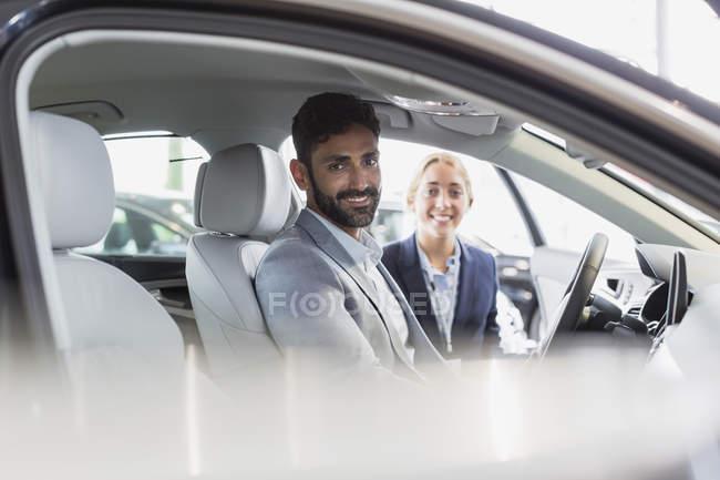 Ritratto sorridente, fiducioso venditore di auto e cliente maschile in driver? s set di auto nuove in concessionaria auto — Foto stock