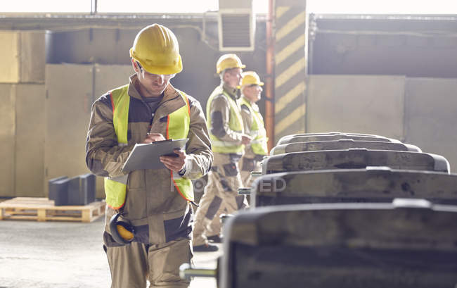 Steelworker writing on clipboard in steel mill — Stock Photo