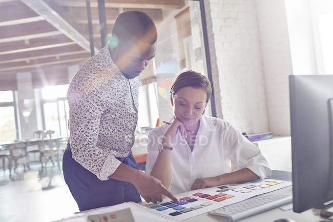 Design professionals discussing color swatches in office — Stock Photo
