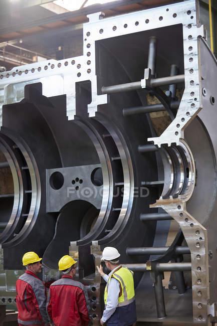 Работники мужского пола, осматривающие большое стальное оборудование на заводе — стоковое фото