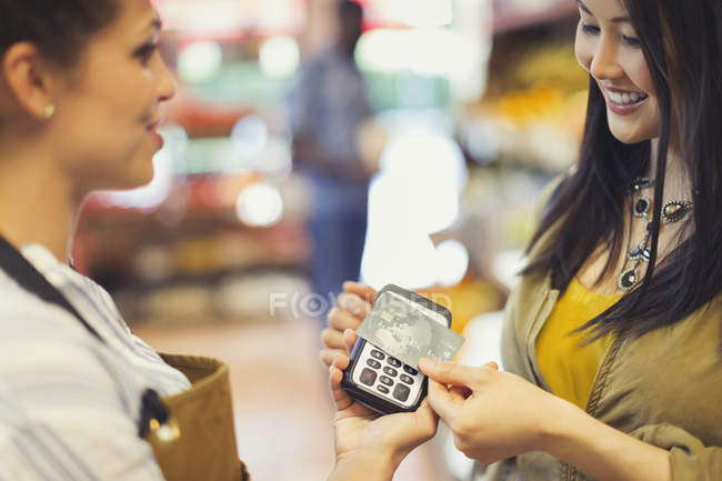 Female customer with credit card using contactless payment in store — Stock Photo