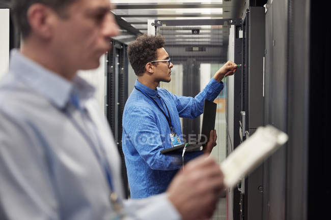 Male IT technicians with clipboard and laptop working at panels in server room — Stock Photo