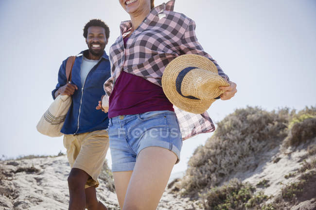 Smiling, enthusiastic couple walking on sunny summer sand beach path — Stock Photo