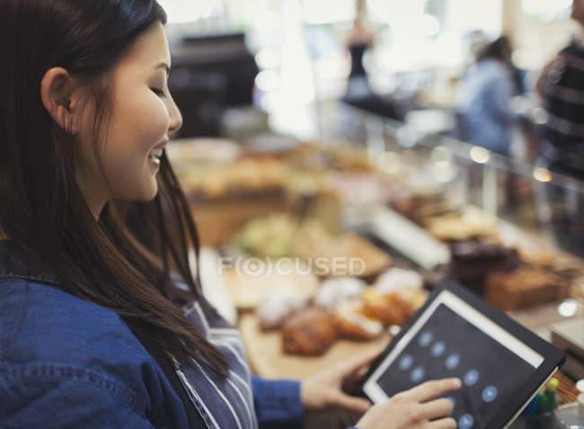 Caissière souriante utiliser touch écran caisse enregistreuse dans café — Photo de stock