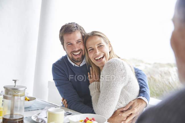 Pareja cariñosa feliz riendo y abrazando en el desayuno de patio - foto de stock