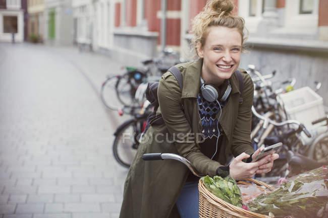 Portrait jeune femme enthousiaste sur le vélo textos sur la rue de la ville — Photo de stock