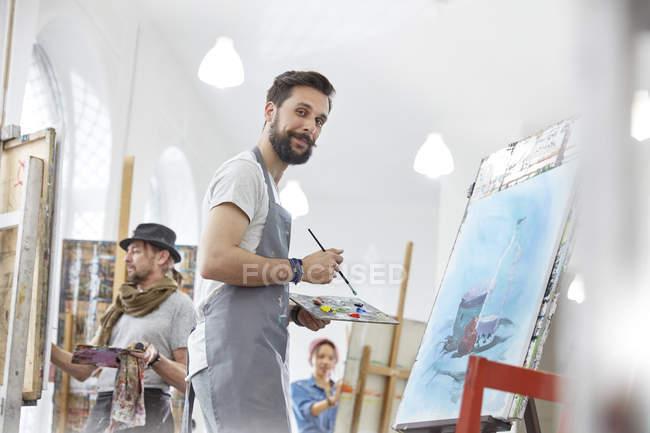 Retrato de artista masculino confiado pintando con paleta en el estudio de la clase de arte - foto de stock