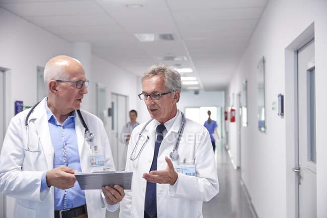 Врачей-мужчин с буфером обмена, что делает раундов, говоря в больничном коридоре — стоковое фото