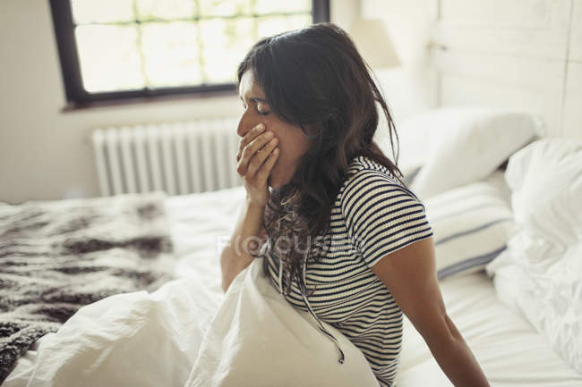 Jovem cansada bocejando na cama — Fotografia de Stock