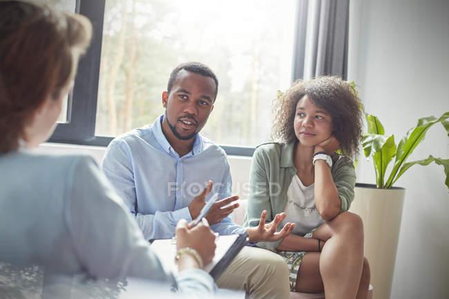 Pareja hablando con terapeuta en sesión de terapia de parejas - foto de stock