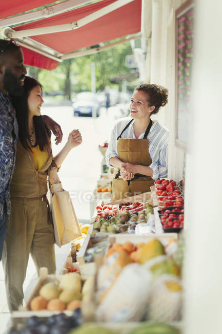 Female worker helping young couple shopping for fruit at market storefront — Stock Photo