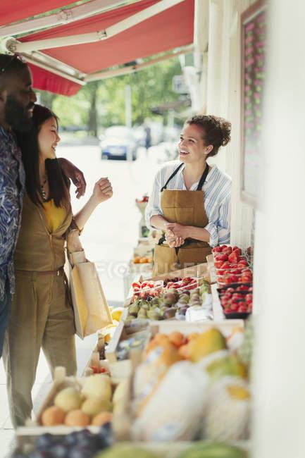 Travailleuse, aider le jeune couple shopping pour les fruits à la vitrine de marché — Photo de stock