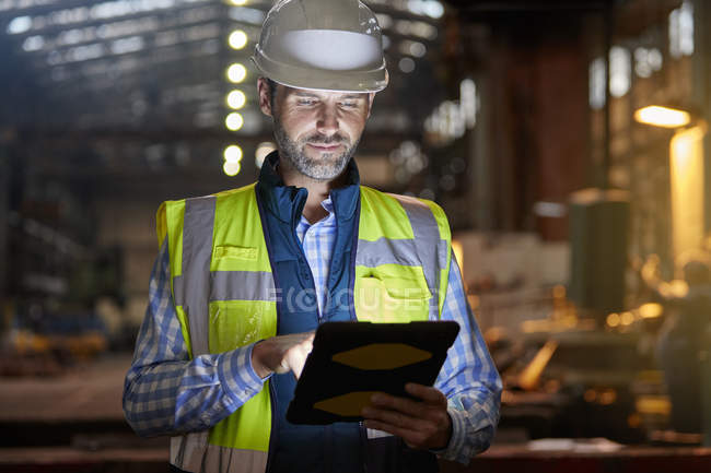 Male engineer working at glowing digital tablet in dark factory — Stock Photo