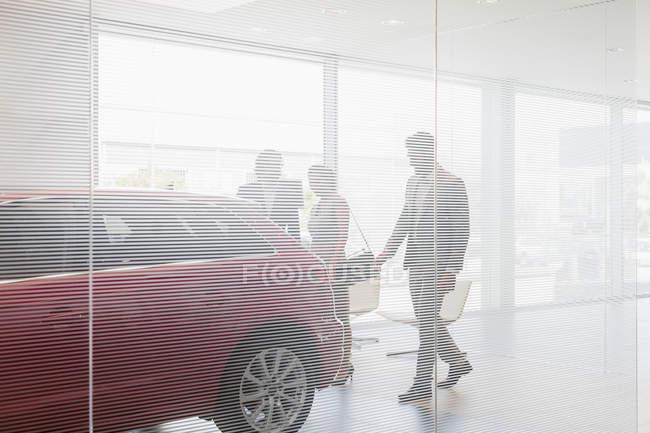 Vendeur de voiture montrant la nouvelle voiture aux clients dans la salle d'exposition de concession de voiture — Photo de stock