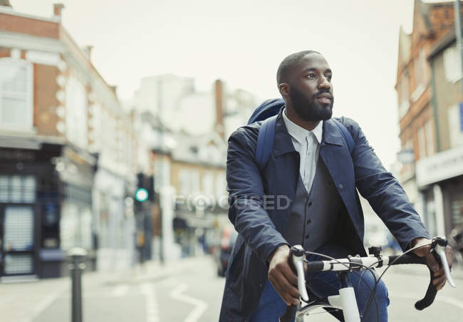 African businessman commuting, riding bicycle on urban street — Stock Photo