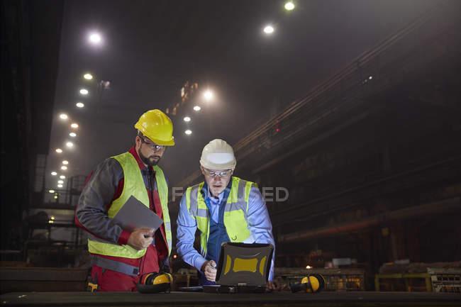 Stahlarbeiter mit Laptop in dunklen Stahlwerk — Stockfoto