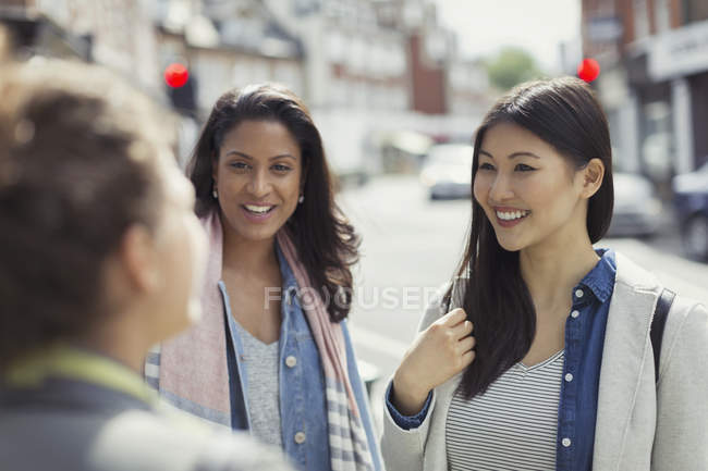 Smiling women friends talking on urban street — Stock Photo