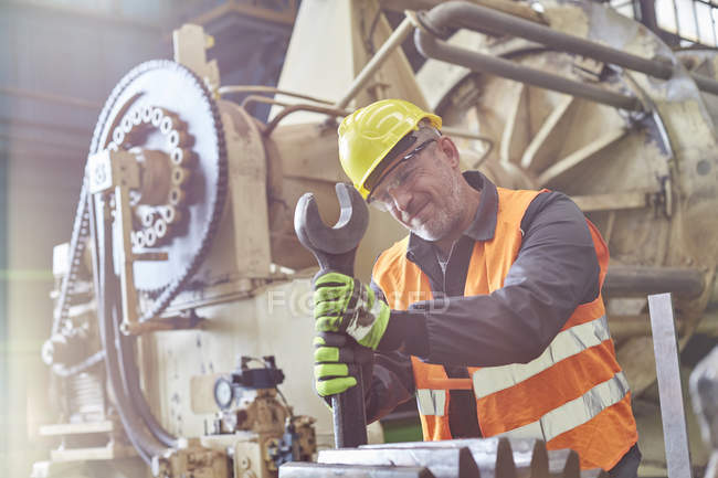 Male worker using large wrench on machinery in factory — Stock Photo