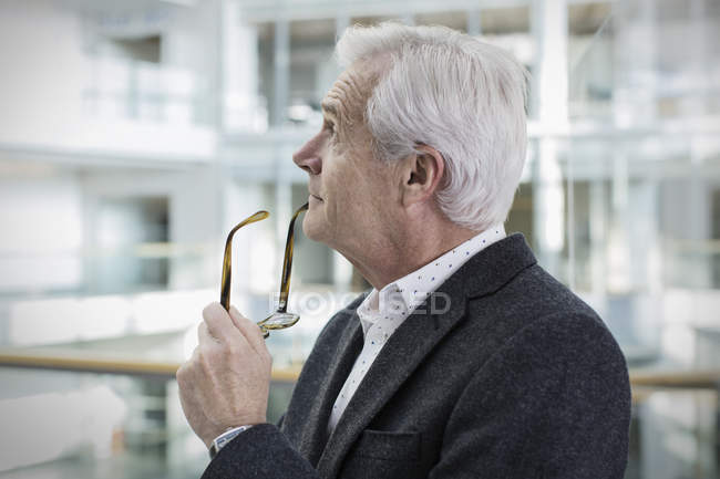 Pensive businessman looking up at modern office — Stock Photo