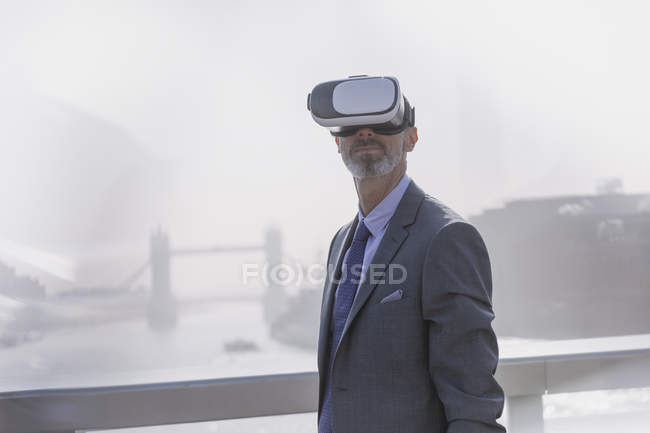 Businessman using virtual reality simulator glasses on sunny urban bridge over Thames River, London, UK — Stock Photo