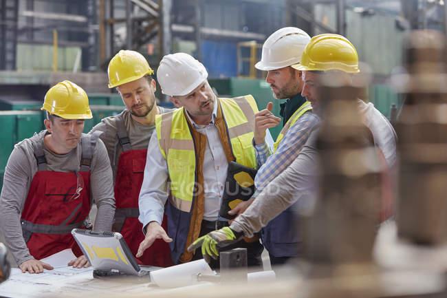 Contremaître masculin, ingénieurs et travailleurs lors d'une réunion sur ordinateur portable, discutant des plans à l'usine — Photo de stock
