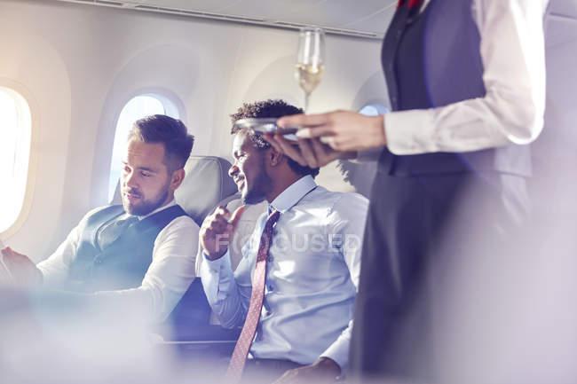 Stewardess serviert Geschäftsleuten in der ersten Klasse Champagner im Flugzeug — Stockfoto