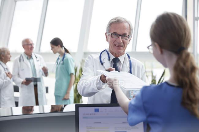 Doctor masculino portapapeles que da a la mujer enfermera en el hospital las enfermeras estación - foto de stock
